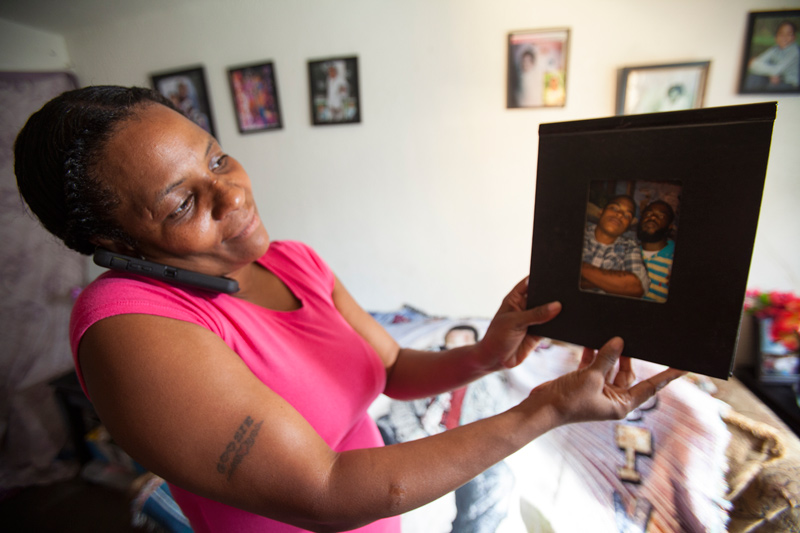 Christina Carstarphen talks to her daughter on the phone while holding a framed photograph of her son, Robert, who was shot and killed in Camden on July 10, 2012. Photo by Erin Patrick O'Connor/ News21.