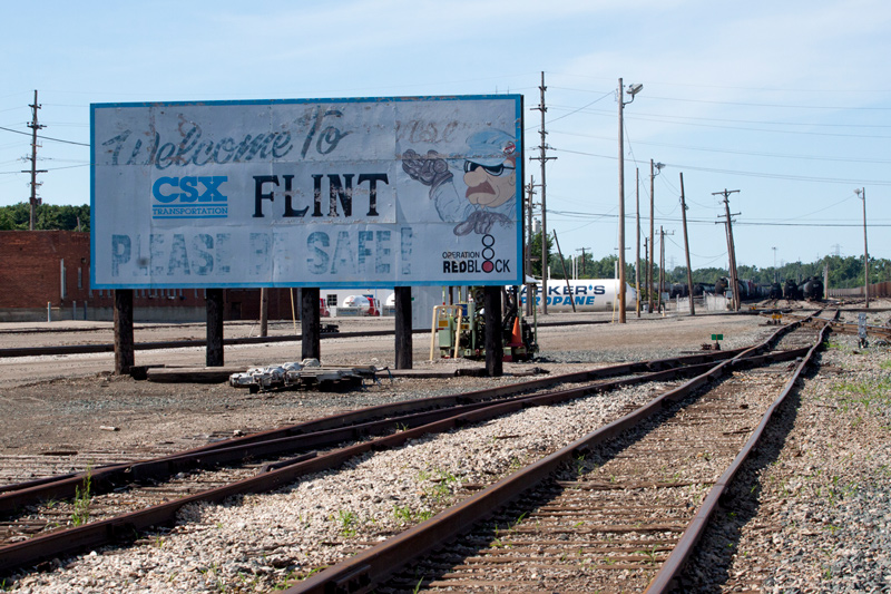 This sign once welcomed new Flint residents by the trainload; now it sits beside the railroad tracks, chipped and deteriorating. Photo by Jackie DelPilar/News21.