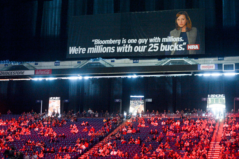 "An NRA convention video labels Michael Bloomberg the group's ""enemy"" given the former New York mayor's million-dollar donations to gun control proponents. Posters echoing the message filled the Indianapolis venue. Photo by Jacob Byk/News21."