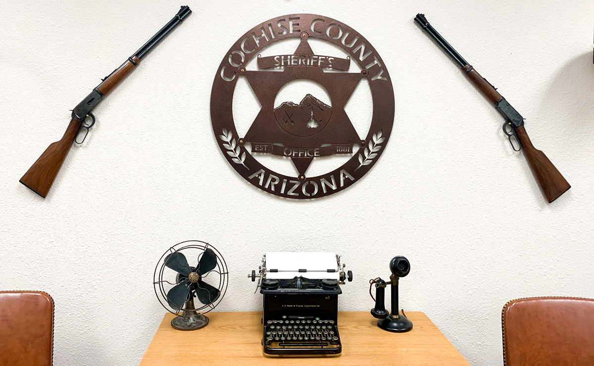 Rifles border the Cochise County Sheriff's seal on a wall at the department headquarters in Bisbee, Arizona. Photo by Terry Greene Sterling/AZCIR